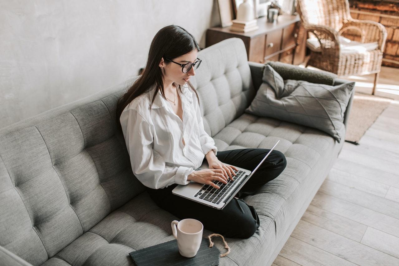 Kvinde slapper af i sofa med computer
