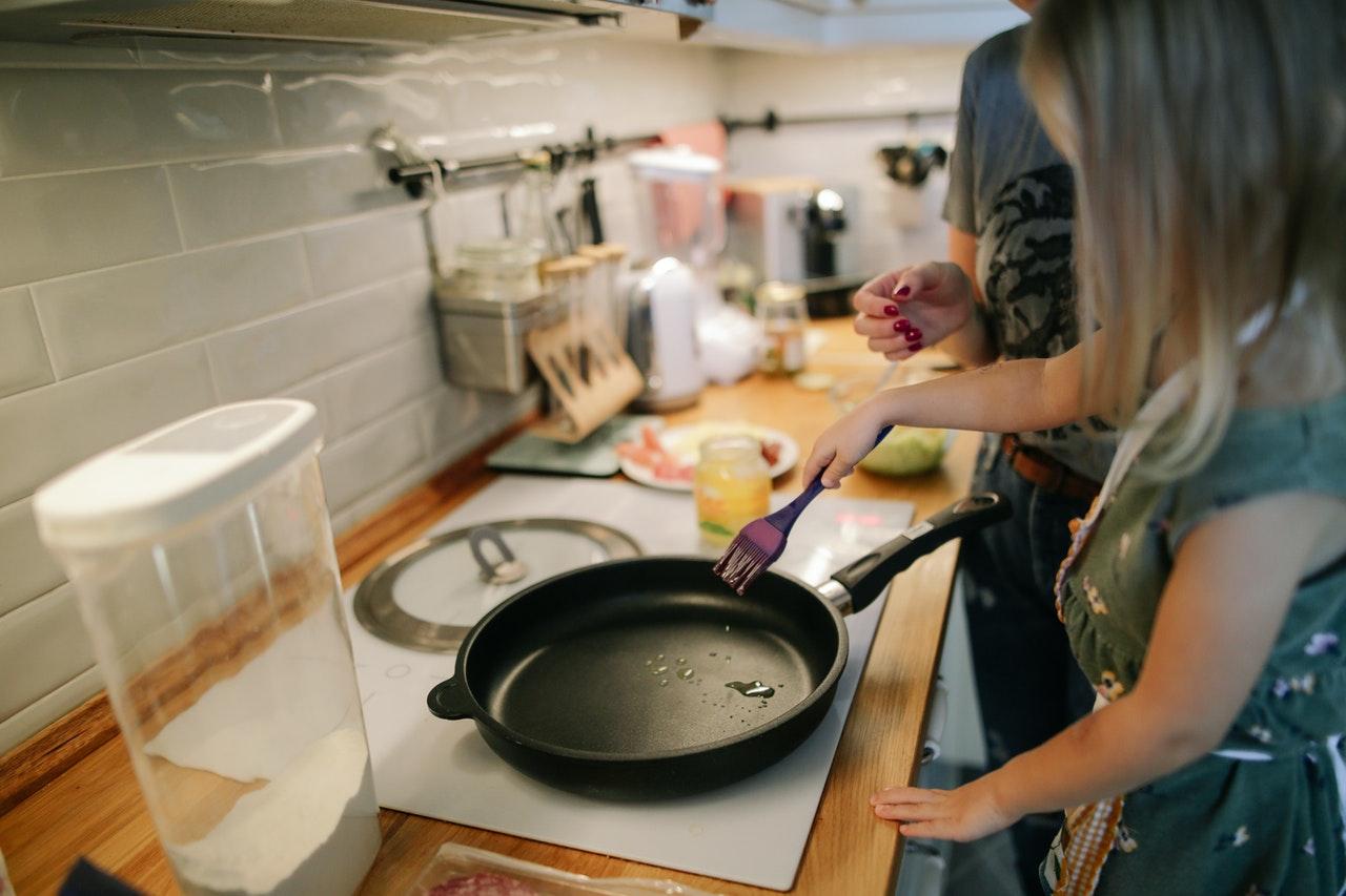Pige og mor laver mad sammen i køkken