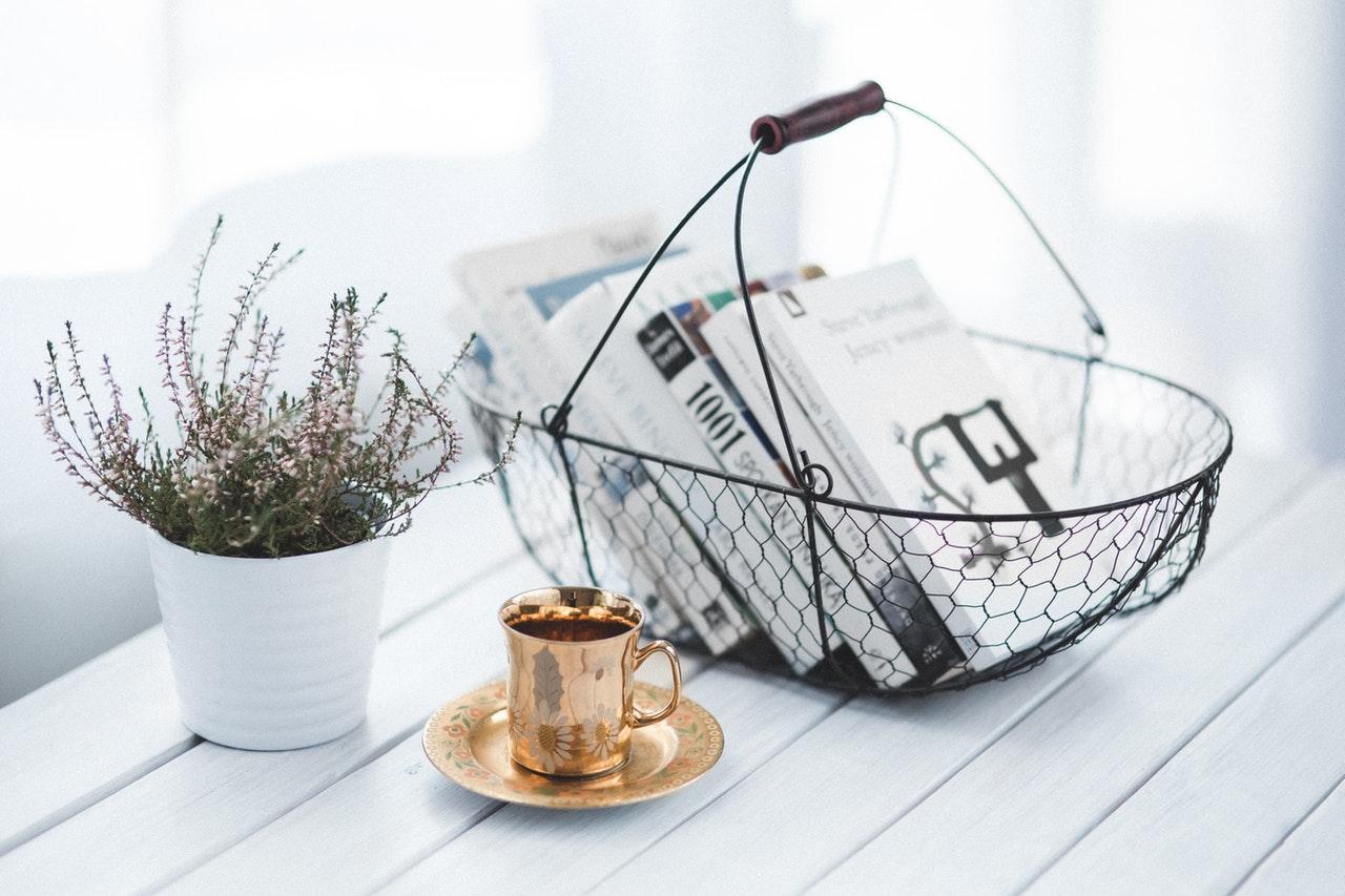 Et hvidt bord med en kurv med bøger i på